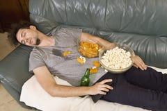 Homem novo cansado que dorme em um sofá com alimento após o partido imagens de stock