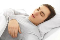 Homem novo cansado que dorme na cama fotografia de stock