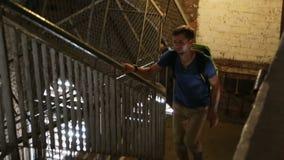 Homem novo cansado que escala as escadas na construção alta, turismo, sightseeing vídeos de arquivo