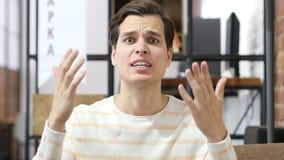 homem novo caucasiano genioso que grita em sua equipe imagem de stock