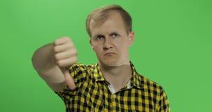 Homem novo caucasiano na camisa amarela que mostra não e que dá seu polegar para baixo fotos de stock