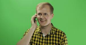 Homem novo caucasiano na camisa amarela usando o telefone celular para a chamada fotografia de stock royalty free