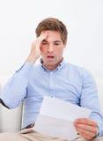 Homem novo chocado lendo a letra Fotografia de Stock