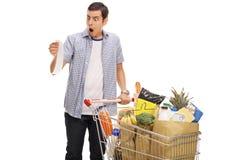 Homem novo chocado que olha um recibo da loja Imagens de Stock