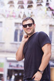 Homem novo com óculos de sol pretos que ri na rua Imagem de Stock