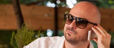 Homem novo com óculos de sol que fala no telefone fotos de stock royalty free