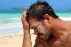 Homem novo com a areia na face pela praia Foto de Stock