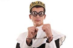 Homem novo com as algemas trajadas na freira para o divertimento, religiou engraçado Fotografia de Stock Royalty Free
