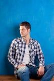Homem novo com as calças de brim da sarja de Nimes da camisa de manta no azul Imagem de Stock