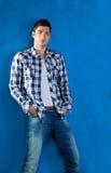 Homem novo com as calças de brim da sarja de Nimes da camisa de manta no azul Fotografia de Stock Royalty Free