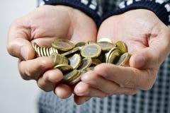 Homem novo com as euro- moedas em suas mãos Fotografia de Stock Royalty Free