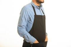 Homem novo com avental preto Fotografia de Stock Royalty Free