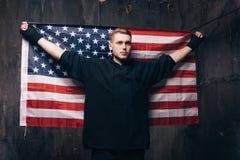 Homem novo com a bandeira nacional dos EUA no estúdio Foto de Stock Royalty Free