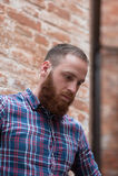 Homem novo com a barba contra o contexto de uma parede de tijolo foto de stock