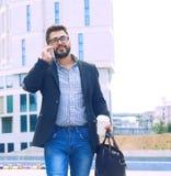 Homem novo com a barba nos vidros que guardam o copo de café e que falam no telefone celular ao andar fora foto de stock