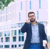 Homem novo com a barba nos vidros que guardam o copo de café e que falam no telefone celular ao andar fora fotografia de stock