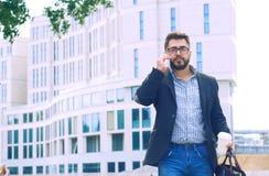 Homem novo com a barba nos vidros que guardam o copo de café e que falam no telefone celular ao andar fora fotografia de stock royalty free