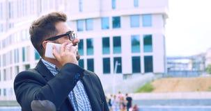 Homem novo com a barba nos vidros que guardam o copo de café e que falam no telefone celular ao andar fora imagens de stock royalty free