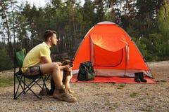Homem novo com a barraca de acampamento próxima do cão imagem de stock