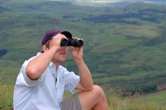 Homem novo com binóculos Fotografia de Stock
