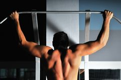 Homem novo com braços fortes que elabora na ginástica Imagem de Stock