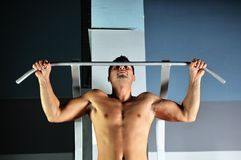 Homem novo com braços fortes que elabora na ginástica Fotos de Stock