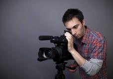 Homem novo com câmara de vídeo video Fotografia de Stock Royalty Free
