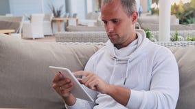 Homem novo com café bebendo do tablet pc no café video estoque