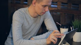 Homem novo com café bebendo do tablet pc no café vídeos de arquivo