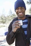 Homem novo com a caneca de café que está no acampamento Imagens de Stock