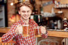 Homem novo com canecas de cerveja Imagem de Stock Royalty Free