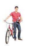 Homem novo com capacete e uma bicicleta Imagens de Stock Royalty Free