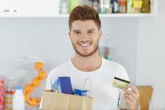 Homem novo com cartão de crédito em casa fotografia de stock