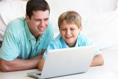Homem novo com a criança no computador portátil Fotos de Stock Royalty Free