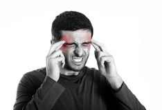 Homem novo com dor de cabeça e enxaqueca de sofrimento da barba na expressão da dor Imagem de Stock Royalty Free