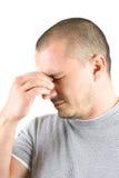 Homem novo com a dor de cabeça isolada no branco Imagem de Stock Royalty Free