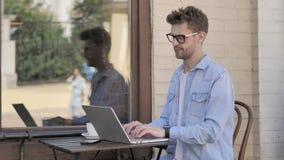 Homem novo com dor de cabeça usando o portátil, assento exterior video estoque