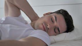 Homem novo com dor de pescoço que dorme na cama vídeos de arquivo