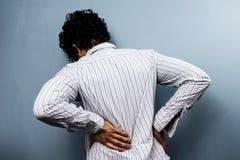 Homem novo com dor nas costas Imagem de Stock