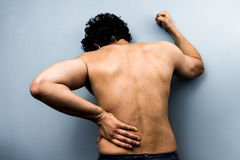 Homem novo com dor nas costas severa da ciática fotos de stock royalty free