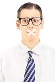 Homem novo com emplastro em seu mounth que gesticula o silêncio Imagem de Stock