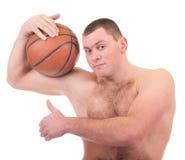 Homem novo com a esfera alaranjada da cesta Imagem de Stock