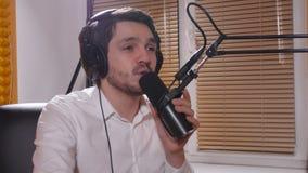 Homem novo com fones de ouvido que fala no mic Rádio em linha e conceito podcasting video estoque