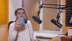 Homem novo com fones de ouvido que fala no mic Rádio em linha e conceito podcasting filme
