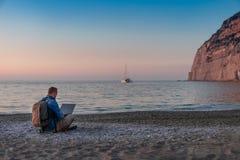 Homem novo com funcionamento do portátil na praia Liberdade, conceitos remotos do trabalho, do freelancer, da tecnologia, do Inte imagem de stock