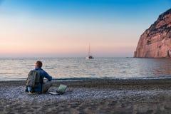 Homem novo com funcionamento do port?til na praia Liberdade, conceitos remotos do trabalho, do freelancer, da tecnologia, do Inte fotografia de stock