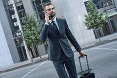 Homem novo com glases que fala no telefone ao andar fora fotos de stock
