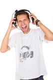 Homem novo com gritaria dos fones de ouvido Fotografia de Stock