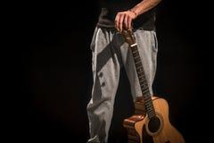Homem novo com a guitarra acústica no fundo preto Foto de Stock Royalty Free