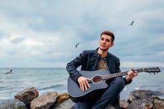 Homem novo com a guitarra acústica que joga e que canta na praia cercada com as rochas no dia chuvoso fotos de stock